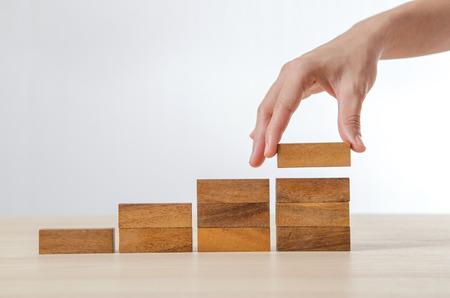 Bliska Kobieta strony organizowanie drewna klocku jako kroku schodów. Proces sukces wzrostu Koncepcja biznesowa. Zdjęcie Seryjne