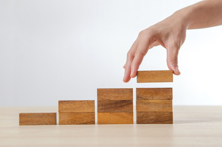 Cierre de mano de la mujer la organización de la madera de apilamiento de bloques como paso de la escalera. Concepto de negocio proceso de crecimiento de éxito. Foto de archivo