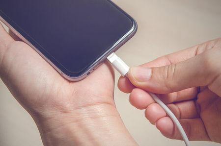 Close up hands holding phone charger