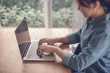 Smiling woman uaing laptop in home office