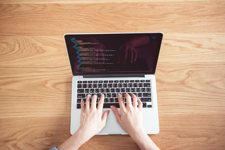 Closeup Woman hands working with coding html and programming on screen laptop with wooden table background, development web, top view.
