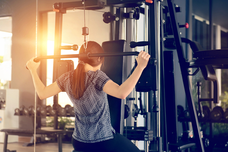 Woman using lat pulldown machine in gym fitness.