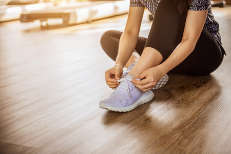 Woman tying running shoes on black floor background in gym fitness with sunlight. copy space.
