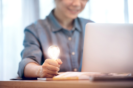 Happy woman holding light bulb while using on laptop, New ideas and creativity concept.