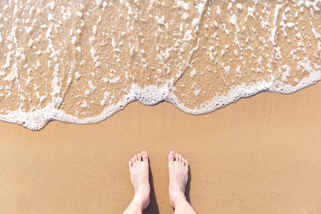 Feet on sea sand and wave with copy space, Vacation on ocean beach, Summer holiday.