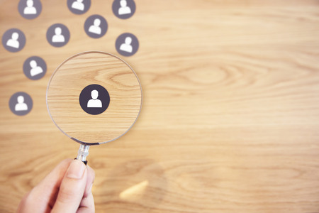 Human resources management and recruitment concept, Hand holding magnifying glass search people paper icon on top desk. Stock fotó
