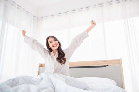 Happy asian woman stretching hands in bed after wake up in the morning, Concept of a new day and joyful weekend.