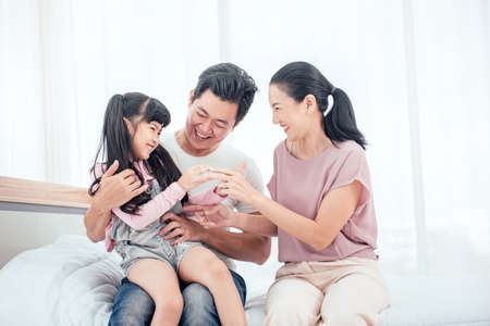Happy Asian family (mother, father, child daughter) playing together on bed while smile in bedroom at home. Imagens