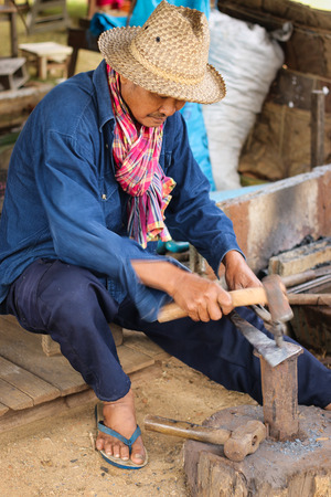 forger: CHIANG MAI THAILAND - DECEMBER 29 2013:A blacksmith forging an iron piece on the anvil