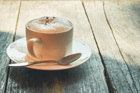 Cup of Cappuccino on wooden slat table with chocolate photo