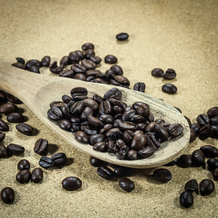 wooden scoop: Coffee beans in an old wooden scoop Stock Photo
