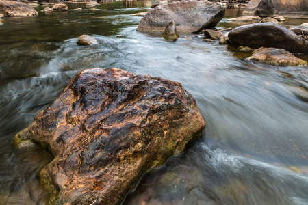 Beautiful River water flowing through stones and rocks at dawn Stock Photo