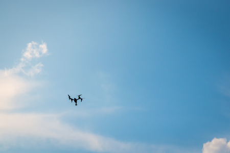 Drone hovering in a bright blue sky
