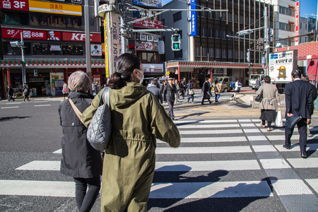 TOKYO, JAPAN - Nov 16, 2017: Travelers are crossing the street at the crosswalk on the Asakusa Road