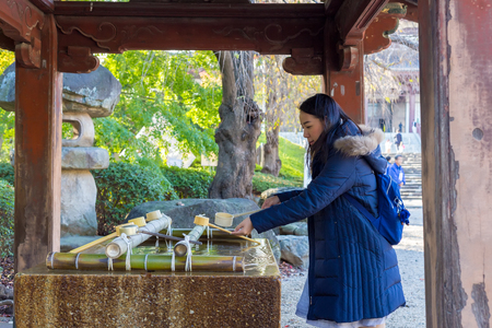 Holy water shrine with tourists scooping water for washing their hands  Editorial