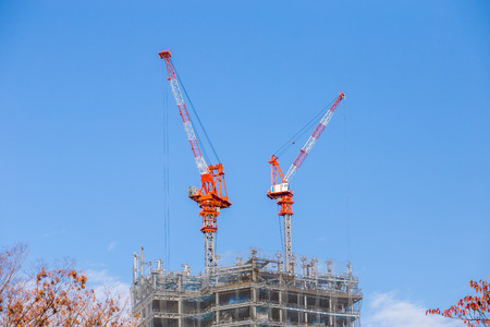 Construction cranes and high rise building under construction against blue sky