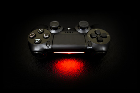 playstation: Bangkok,THAILAND, -24 APRIL 2016 : The new Sony Dualshock 4 with PlayStation 4 on leather Black. Sony PlayStation 4 game console of the eighth generation. Editorial