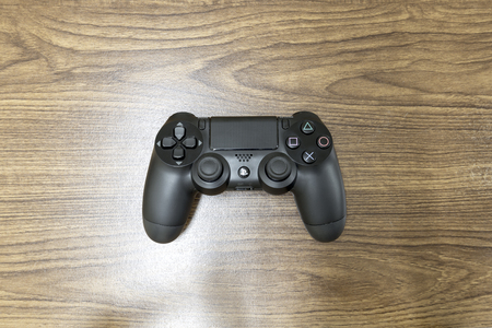 ps: Bangkok,Thailand, -17 May 2016 : The new Sony Dualshock 4 with PlayStation 4 on Wood front view. Sony PlayStation 4 game console of the eighth generation.