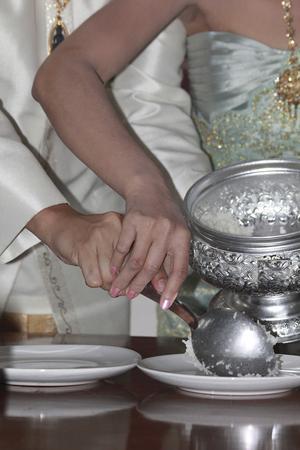 Thaise traditie bruiloft. Een cuple geven voedsel aan de monniken. Beide nemen rijst in de plaat. Stockfoto