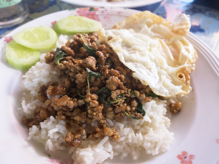 white rice wth pork basil stir fry with fry eggs and cucumber Banco de Imagens