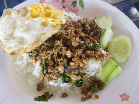 pork basil stir fry with fried eggs and white rice