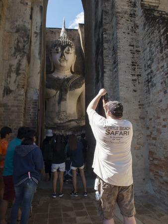 a tourist taking photo a big buddha statue Sukhothai Historic Park Stock Photo - 97040443