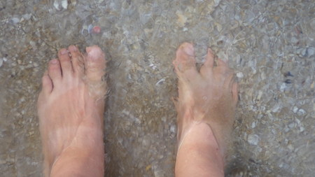 human feet stand in clear water Stockfoto
