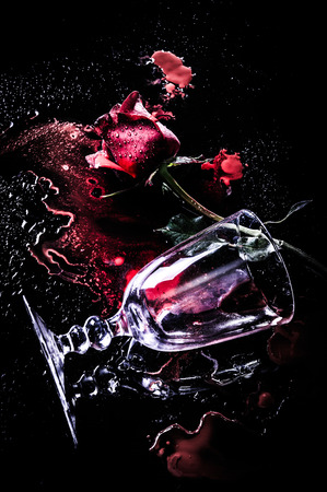 dramatic a red rose with wine glass on blood