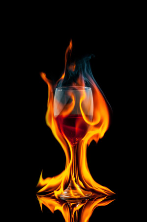 sconce: glass of wine on black background with fire splash Stock Photo