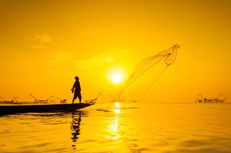 throwing fishing net during sunset , thai 免版税图像