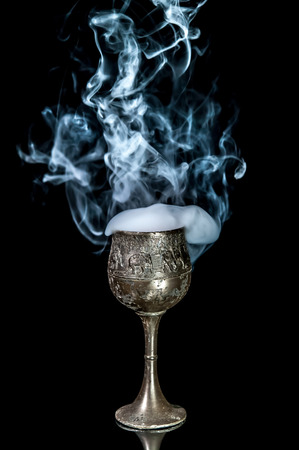 chalices: Wine goblet with smoke on black background Stock Photo