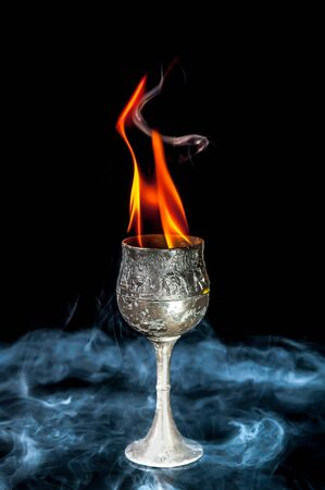 chalices: Wine goblet with Fire flames with smoke on black background Stock Photo