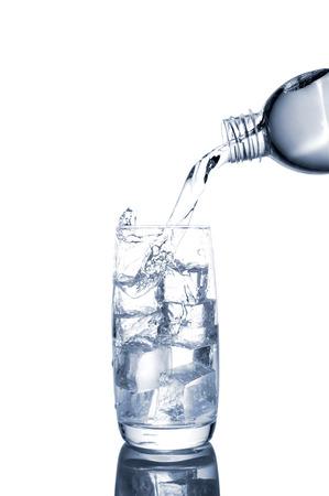 vaso de agua: vertiendo el agua en un vaso sobre un fondo blanco Foto de archivo