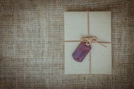 gunny: Gift boxes with labels made of leather with rope on gunny sack vintage style background Stock Photo
