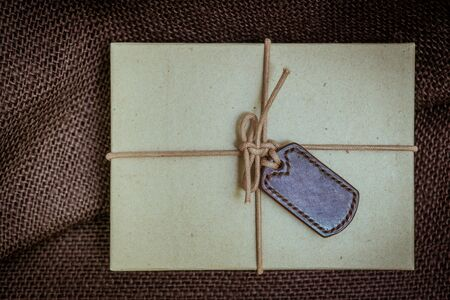 christmas baker's: Gift boxes with labels made of leather with rope on gunny sack vintage style background Stock Photo