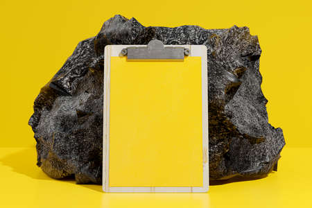 Clipboard Mock-Up yellow color front of the black stone. 3d Render.
