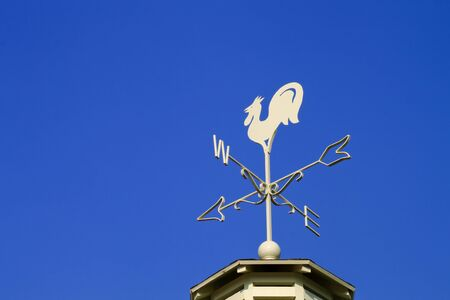 Wind vane in a form of a rooster on the top of a roof. photo