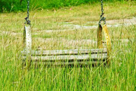 swing seat: Un altalena in legno e seduta in altalena erba in un campo estivo