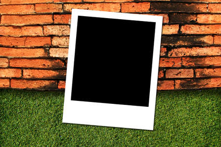 Photo frame on green grass and brick wall background  photo