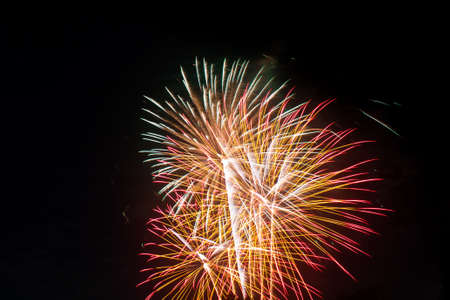 emanate: Brightly colorful fireworks in the night sky. New Year celebration fireworks.