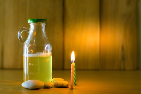Beer bottle and fire of candles put on wood with wooden background using wallpaper for party at night.