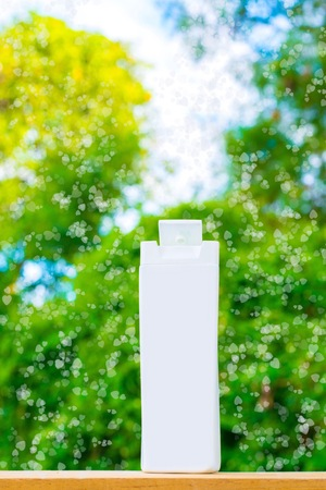 dispenser: plastic bottle white on the wood and tree blurry bokeh background in garden. Using wallpaper for package work photo.