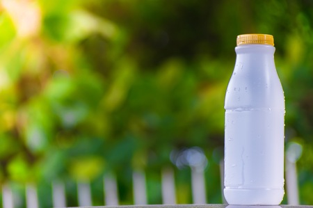 plastic bottle white on the wood and tree blurry bokeh background in garden. Using wallpaper for package work photo.