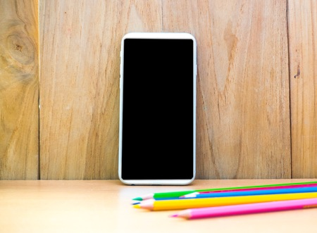 white wood floor: Smartphone with pencil on wood board background. using wallpaper or background for education, business photo. Take note of the product for book with paper and concept or copy space. Stock Photo