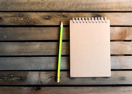 Notepad with pencil on wood board background.using wallpaper for education, business photo.Take note of the product for book with paper and concept, object or copy space.
