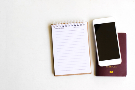 white sheet: Notepad with passport and smartphone on wood board background.using wallpaper for education, business photo.Take note of the product for book with paper and concept, object or copy space.