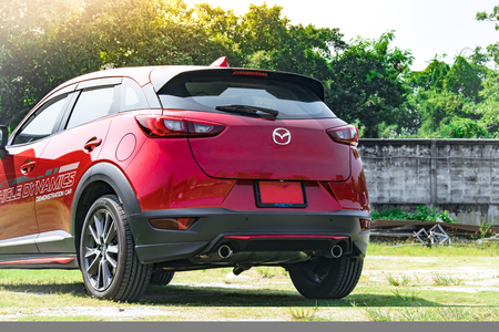 keyless: BANGSAN, THAILAND - OCTOBER, 29, 2017 :  Test drive car mazda brand japan parked on lawn with tree blurry background in showroom of thailand for customers. Editorial