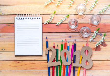notepad with number paper 2018 on wood background using wallpaper or background for happy