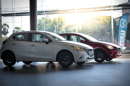 BANGSAN, THAILAND - DECEMBER 9, 2017 :  This car all new mazda 2 and mazda 3 brand japan white, red color parked in showroom of thailand for customers.