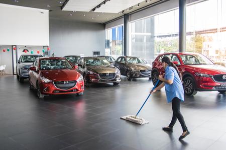 BANGSAN, TAILANDIA - 4 GENNAIO 2018: Le donne stanno pulendo il pavimento nella marca di Mazda dell'automobile dello showroom della Tailandia per l'immagine editoriale di trasporto. Archivio Fotografico - 93181817